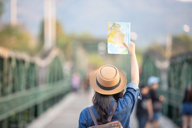 Female tourists on hand have a happy travel map.